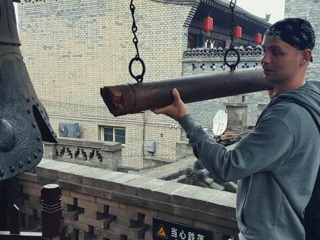 Bloger podróżniczy uderza w dzwon w Pingyao w Chinach.