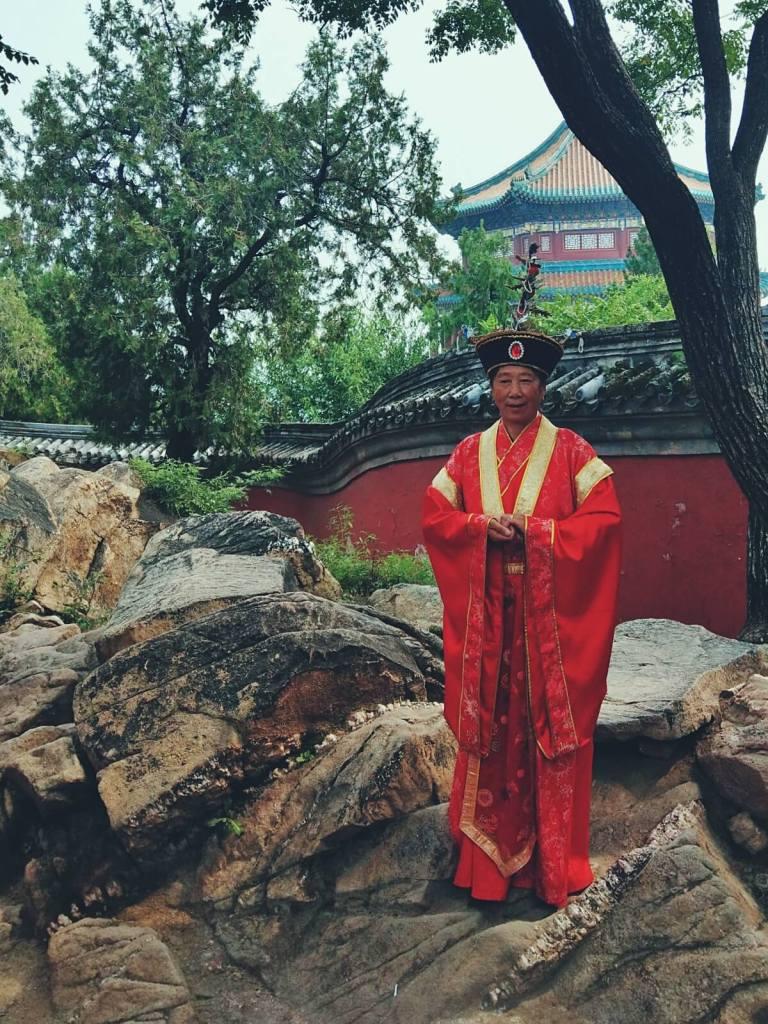 Mężczyzna pozujący przed Pałacem Letnim w Pekinie.