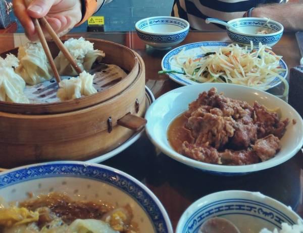 Stół zastawiony chińskim jedzeniem.