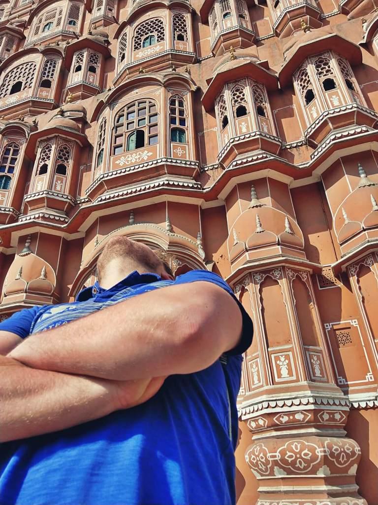 Bloger podróżniczy patrzy na Pałac Wiatrów w Dżajpurze w Indiach.