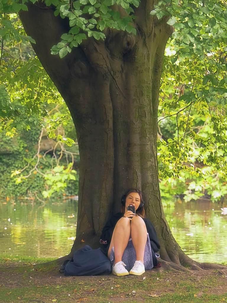 Dziewczyna odpoczywająca pod drzewem w parku.
