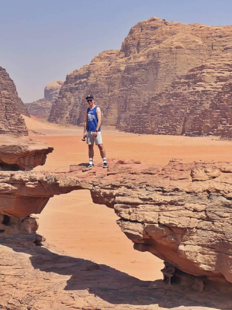 Bloger podróżniczy na małym łuku w Wadi Rum.