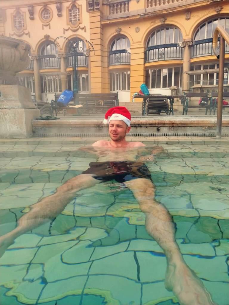 Mężczyzna w czapce Mikołaja w gorących źródłach w Budapeszcie.