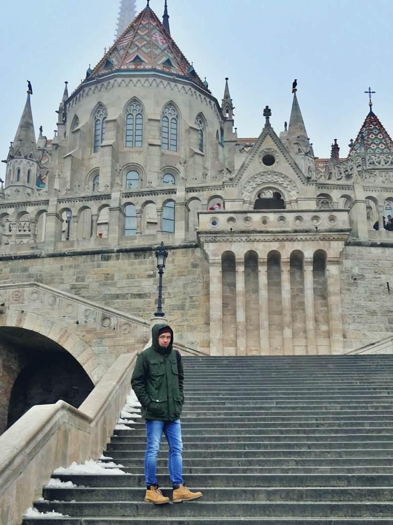 Bloger podróżniczy pozuje przy baszcie Rybackiej w Budapeszcie.
