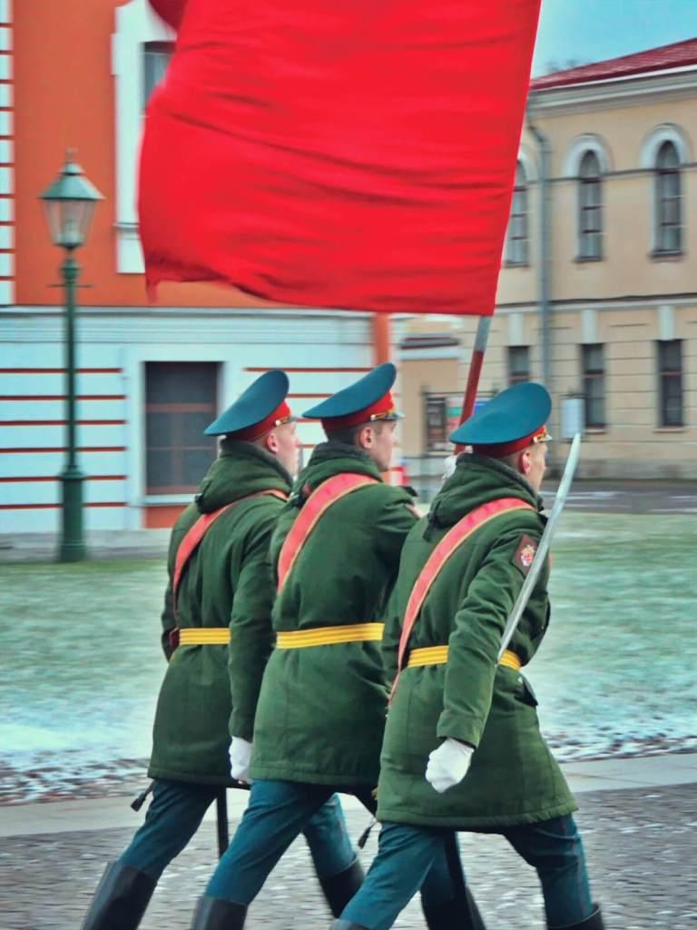 Rosyjscy żołnierze maszerują z flaga.