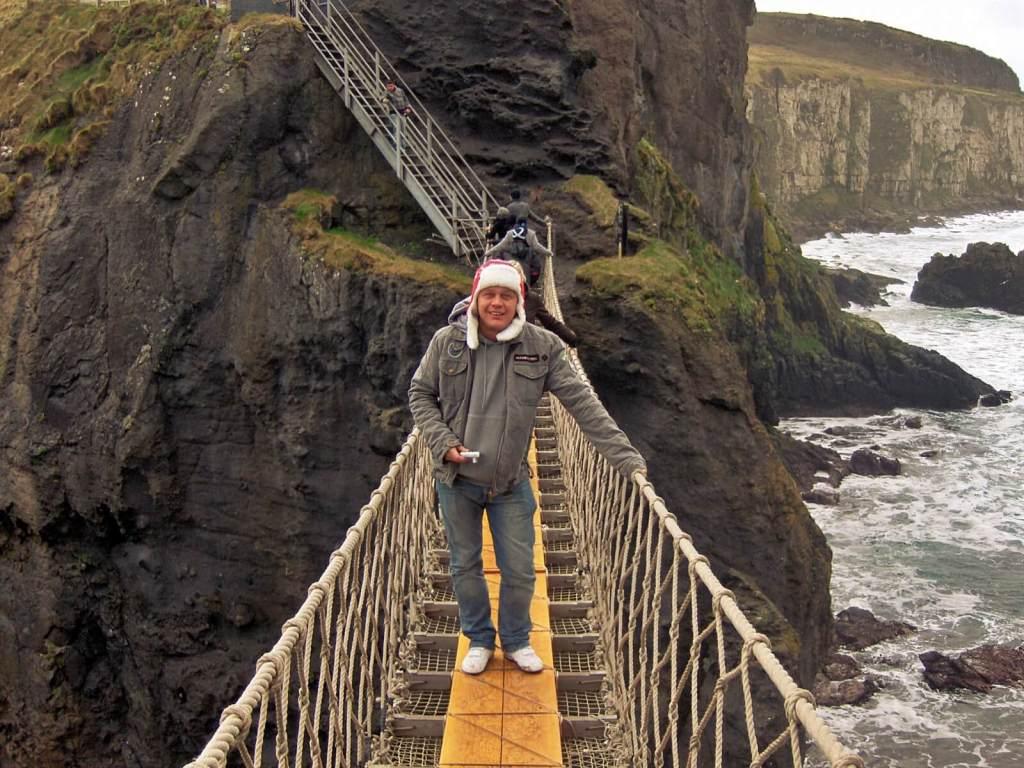 Bloger podróżniczy na mocie linowy nad oceanem w Irlandii Północnej.
