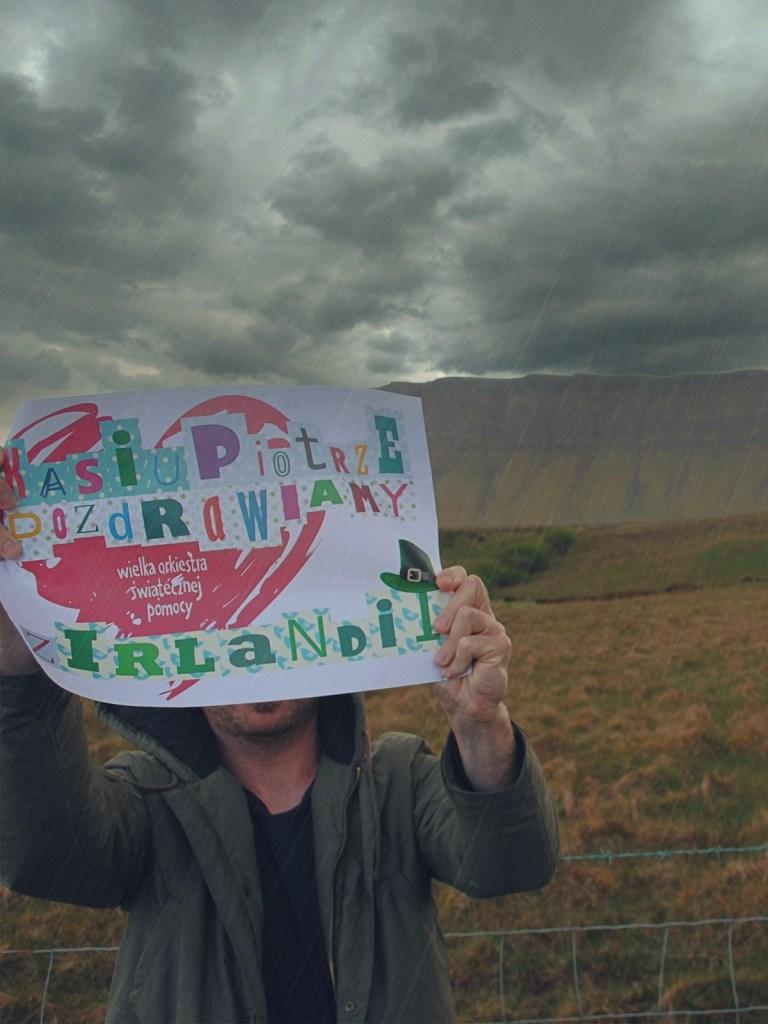 Bloger podróżniczy pozuje z plakatem na tle góry Ben Bulben w Sligo, w Irlandii.
